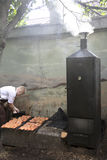 A cook smokes salmon outside of restaurant. ESTONIA, TALLINN, JUNE, 21, 2014 - Cook lays out the pieces of salmon on a grate for smoking outside of restaurant in Stock Images