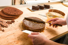 Cook spreading sauce on cake in kitchen royalty free stock image