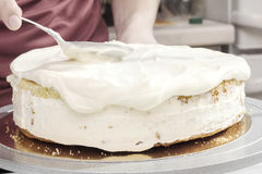 Cook spreads cream on the cake Royalty Free Stock Photography