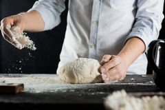 Cook sprinkles dough with flour on the kitchen table royalty free stock images