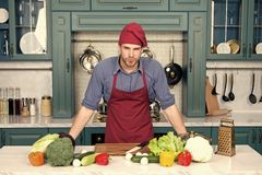 Cook stand at kitchen table. Man in chef hat and apron in kitchen. Vegetables and tools ready for cooking dishes. Vegetarian menu and healthy diet. Food royalty free stock images