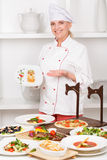 Cook stands before the table with meals Stock Photography