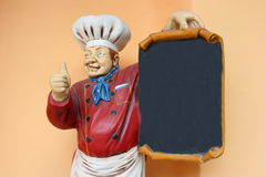 Cook statue. With blank menu black board Stock Photos