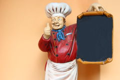 Cook statue. With blank menu black board Royalty Free Stock Image