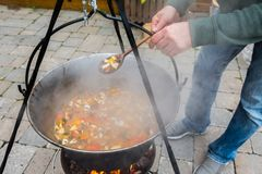 Cook stirring soup in a cauldron stock photos