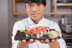 Cook stretches out a plate with sushi Royalty Free Stock Image