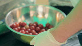 Cook stringing on skewers cherry tomatoes, mozzarella and sauce in a container stock footage