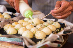 Cook stuffing dough or rice balls at street market Stock Images