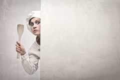 Cook Surprise. Woman cook behind a white wall with a wooden spoon Stock Photo