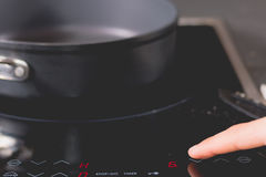 Cook is switching on the induction cooktops Royalty Free Stock Photos