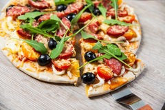 Cook takes a shovel one piece of pizza with cheese olives and salami, mushrooms and tomatoes, arugula. On a wooden stand Royalty Free Stock Images