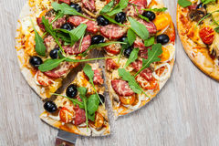 Cook takes a shovel one piece of pizza with cheese olives and salami, mushrooms and tomatoes, arugula. On a wooden stand Royalty Free Stock Photography