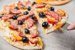 Cook takes a shovel one piece of pizza with cheese olives and salami, mushrooms and tomatoes. On a wooden stand Stock Photography