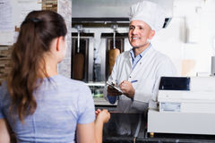 Cook taking order from customer in fast-food cafe. Mature men cook wearing uniform taking order from customer in fast-food cafe counter Stock Images