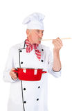 Cook taste the food. Cook is tasting the food with wooden spoon and red pan Royalty Free Stock Photography