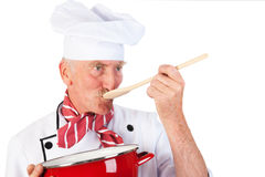 Cook taste the food. Cook is tasting the food with wooden spoon and red pan Royalty Free Stock Photo