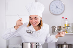 Cook tasting food. Smiling woman cook tasting delicious dishes in kitchen Stock Images
