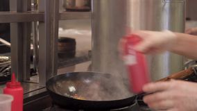 Cook time cooking paste adds sauce from the bottle and stirs. In the restaurant, the chef prepares spaghetti with vegetables and takes a dressing to make the stock footage