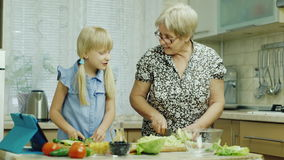 Cook together. The girl of 6 years helps her grandmother in the kitchen, watching the salad recipe on the tablet stock footage