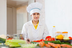Cook  in toque works with tomato and other vegetables Stock Images