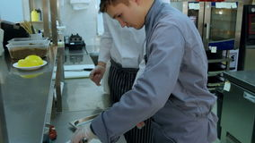 Cook trainee learning to serve vegetables on a plate stock footage
