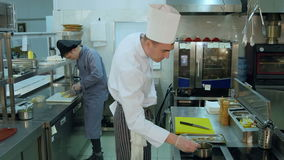 Cook trainee slicing lemon while chef spicing shrimps stock video footage