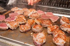Cook turn around grilled meat Royalty Free Stock Image