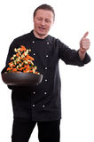 Cook is turning the vegetables in a pan and thumb Stock Images