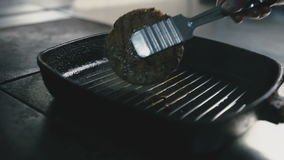 Cook turns the cutlet in a frying pan close-up stock footage