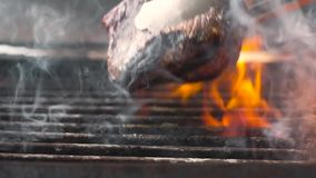 Cook turns the meat on a hot grill. Slow motion, close up.  stock footage