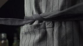 Cook tying a kitchen apron in the kitchen. Side view stock video footage