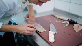 The cook unbones the fish fillet at the board. With a tweezers stock footage