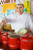 Cook in uniform spoon imposes soup in plate Royalty Free Stock Photography