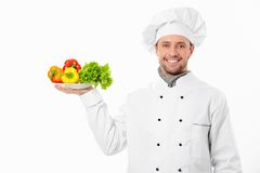 The cook with vegetables. Young cook holding a plate with vegetables on white background Stock Image