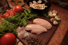Cook vegetables and chicken. Love to healthy eating concept. Cooked  chicken , mushrooms and a salad of tomatoes, cucumbers and greens. Proper nutrition. love to Stock Photos