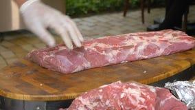 Cook w białych rękawiczkach ciie daleko kawałki stki od wielkiego kawałka surowy mięso Ilości wieprzowiny tenderloin dla zbiory wideo