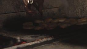 Cook w restauracyjni dłoniaki ciąć cebulach na bbq grillu w ceglanym piekarniku nad węglami w slowmo, zakończenie w górę pokrojon zdjęcie wideo
