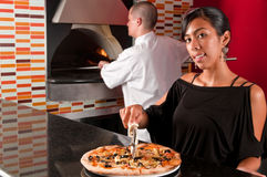 Cook and waitress. Waitress cutting a pizza while coworker cook works in the oven baking Stock Photos