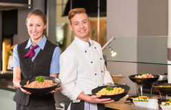Cook and waitress from catering service posing in front of buffe. Cook or chef and waitress from catering service posing with food in front of buffet Royalty Free Stock Images