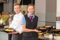 Cook and waitress from catering service posing in front of buffe Stock Photos