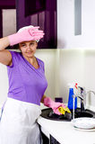 Cook wiping her brow as she does washing up Royalty Free Stock Photo