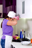 Cook wiping her brow as she does washing up Stock Image