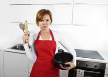 Cook woman in angry upset frustrated face expression in apron ho Stock Photography
