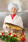 Cook woman with carp Stock Photography