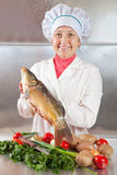 Cook woman with carp fish Royalty Free Stock Images