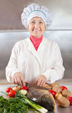 Cook woman with carp fish Stock Photography