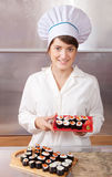 Cook woman with cooked sushi rolls royalty free stock photo
