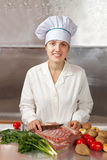 Cook woman  cooking meat Royalty Free Stock Images