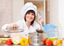 Cook woman   cooks  with ladle in kitchen Royalty Free Stock Photos