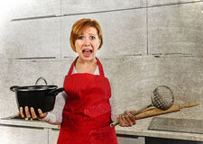 Cook woman desperate in stress in apron holding cooking pot at home dirty edit. Young attractive cook woman desperate in stress in apron holding cooking pot and Royalty Free Stock Photography